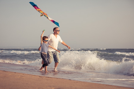 Foto de Father and son playing on the beach at the day time. People having fun outdoors. Concept of summer vacation and friendly family. - Imagen libre de derechos