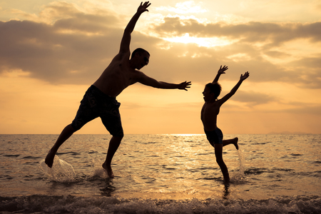 Foto per Father and son playing on the beach at the sunset time. People having fun outdoors.  Concept of happy vacation and friendly family. - Immagine Royalty Free