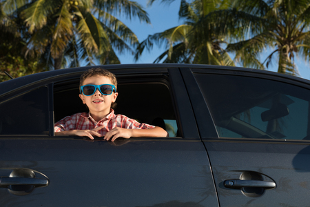 Photo pour One happy little boy sitting in the car at the day time. Concept of summer vacation. - image libre de droit