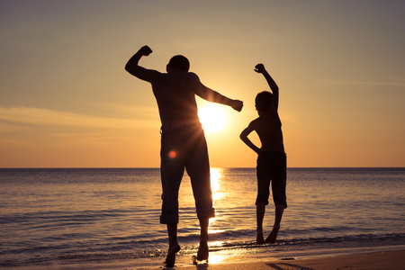 Photo pour Father and son  playing on the beach at the sunset time. People having fun outdoors. Concept of summer vacation and friendly family. - image libre de droit