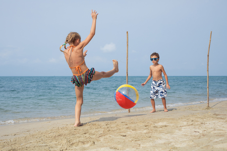 Photo for Two happy little children playing on the beach at the day time.  Kids having fun outdoors. Concept of kids on vacation and friendly family. - Royalty Free Image