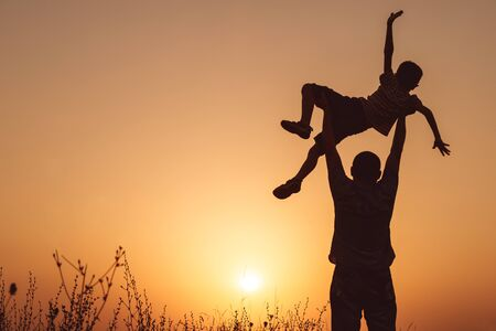 Photo for Father and son playing in the park at the sunset time. People having fun on the field. Concept of friendly family and of summer vacation. - Royalty Free Image