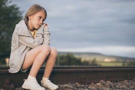 Photo for Portrait of young sad girl sitting outdoors  on the railway at the day time. Concept of sorrow. - Royalty Free Image