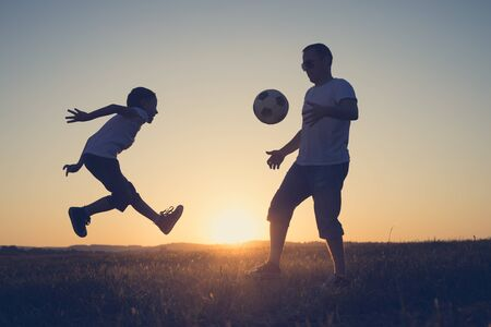 Photo pour Father and young little boy playing in the field  with soccer ball. Concept of sport. - image libre de droit
