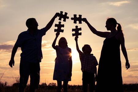 Photo for Happy family standing in the park at the sunset time. People having fun outdoors. Concept of friendly family. - Royalty Free Image