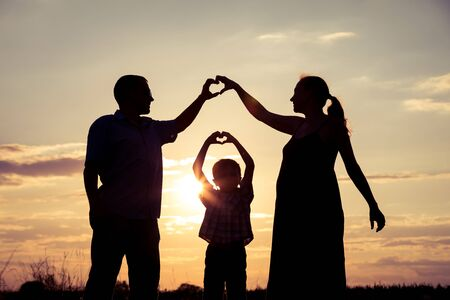 Foto für Happy family standing in the park at the sunset time. People having fun outdoors. Concept of friendly family. - Lizenzfreies Bild