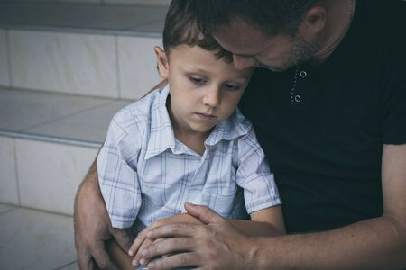 Photo for Portrait of young sad little boy and father sitting outdoors at the day time. Concept of sorrow. - Royalty Free Image