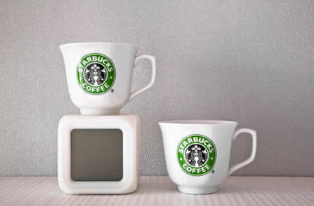 Kiev, Ukraine - February 16, 2016: Two ceramic shiny white cups with stylish round green logo of Starbucks coffeehouse corporation and square cube shape electronic clock on modern shelf, copy space