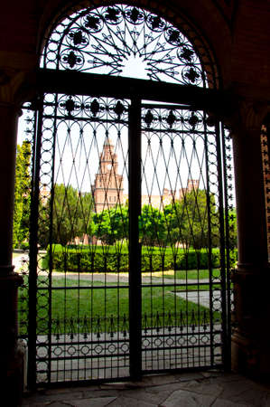 beautiful historical building of Chernivtsi national university religious seminary of red brick facade with green trees and bushes behind iron gates sunny outdoor in Ukraine