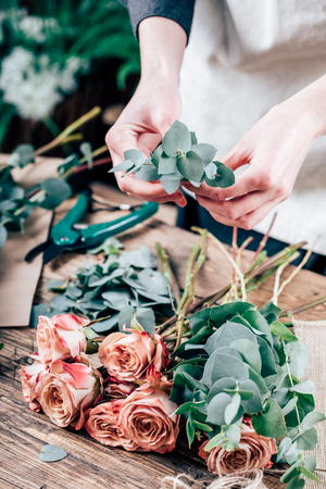 Florist working on the workspace in flower shop to create bouquet