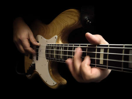 bassist playing bass isolated over black background