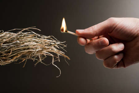 male hand holding a match in the act of lighting a tuft of straw