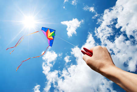 kite flying in a beautiful sky with sun and clouds