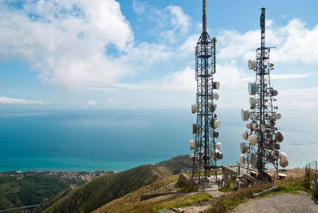 panorama with two telecommunications towers against sea and sky