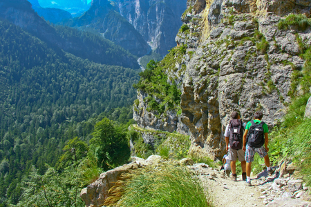 travellers two adult men stopped for rest and looking on the rock wall of dolomites Alps in Italy
