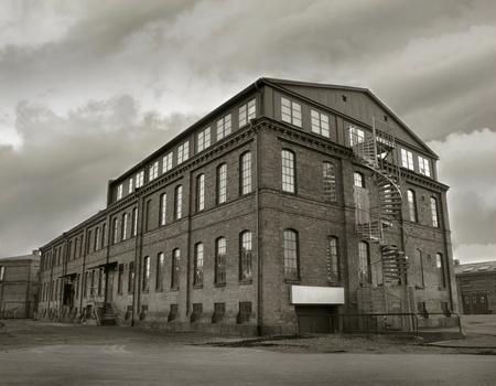 Old depressing factory building in sepia tone. Symbol for economic depressions.