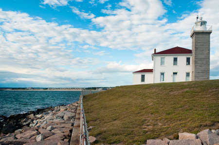 Watch Hill Lighthouse guides mariners along its rocky shoreline in Rhode Island.
