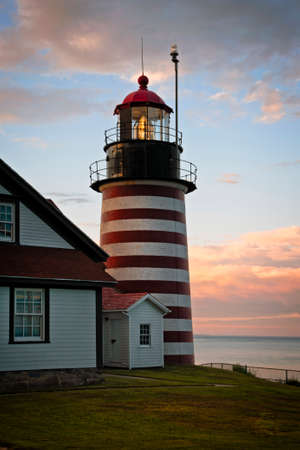 Photo pour Authentic fresnel lens of West Quoddy head lighthouse, famous for its red and white srtipes, shines brightly during sunset in northern New England. It is the easternmost beacon in America. - image libre de droit