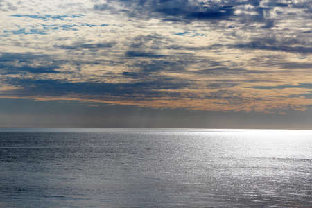 Silvery ocean  on a  late  cloudy afternoon in winter