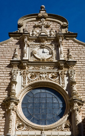 Montsarat monetarily church building exterior showing statues, clock, and window