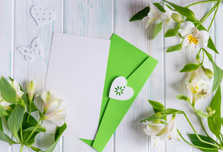 Photo pour Mock up blank paper, mail envelope on a white wooden background with natural flowers of white color and butterflies. Blank, frame for text. Greeting card design with flowers. - image libre de droit
