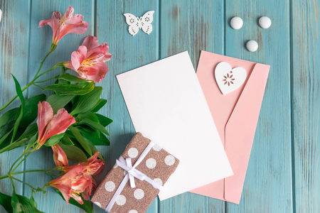 Photo pour Mock up blank paper, mail envelope on a blue wooden background with natural flowers of pink color and butterflies. Blank, frame for text. Greeting card design with flowers. Aalstroemeria on wooden background. - image libre de droit