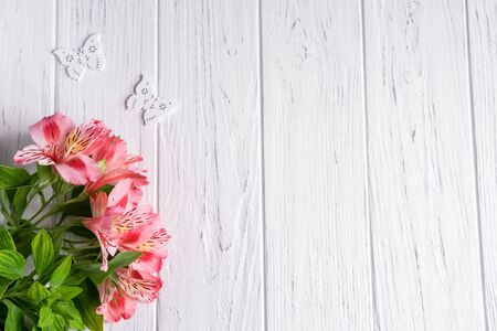 Photo for Background for text banner on a light wooden background with pink flowers and butterflies. Blank, frame for text. Greeting card design with flowers. Alstroemeria on wooden background. - Royalty Free Image