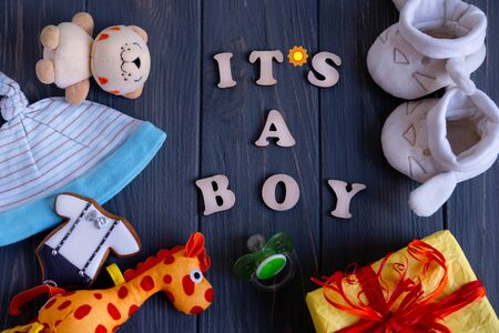 Photo pour This is a boy. Greeting card with an inscription of wooden letters with toys for newborns, a box with a gift on a gray dark wooden background. Greeting card for newborns in dark colors. - image libre de droit