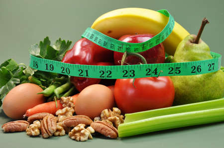 Group of wholesome, organic food, including pear, apple, tomato, eggs, nuts, pecans, walnuts, carrot, banana, and apple, for a healthy diet or slimming New Year resolution