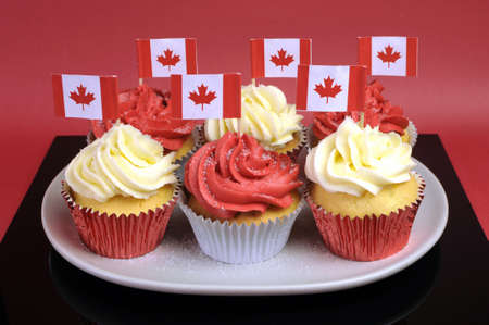 Red and White cupcakes with Canadian maple leaf national flags against a red background for Canada Day or Canadian national holidays. Close-up.
