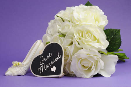 Wedding bouquet of white roses with good luck high heel shoe and heart sign with Just Married message, against purple lilac background の写真素材
