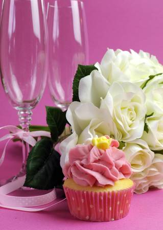 Wedding bridal bouquet of white roses on pink background with pink cupcake and pair of two champagne flute glasses. Vertical.の写真素材