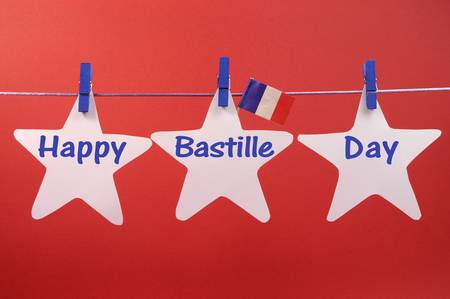 Happy Bastille Day written across white stars hanging from pegs on a line, with French flag, for France public holiday on 14 July
