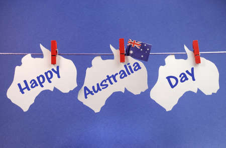 Celebrate Australia Day holiday on January 26 with a Happy Australia Day message greeting written across white Australian maps and flag hanging pegs on a line against a blue background