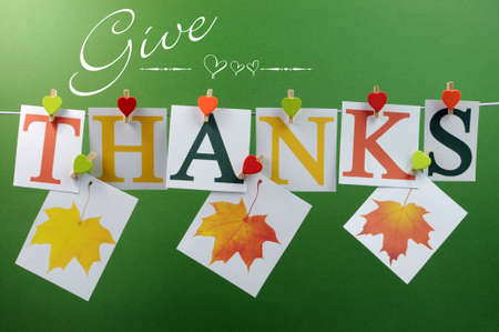 Give Thanks message spelling in letters hanging from pegs on a line for Thanksgiving greeting in autumn colors, with autumn fall leaves