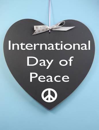 International Day of Peace message written on heart shape blackboard with peace sign against a sky blue background