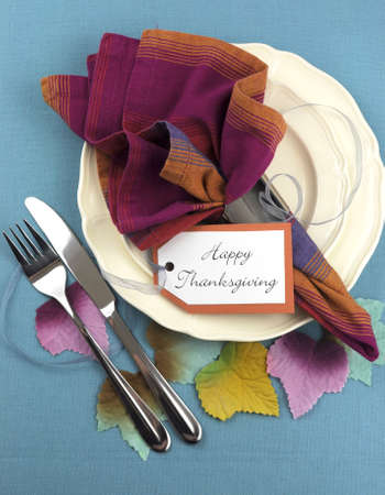 Modern Thanksgiving dining table place setting on aqua blue tablecloth, with material autumn leaves, in pink blue and orange theme. Vertical aerial view.