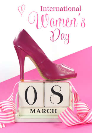 Beautiful female icon pink high heel shoe with vintage shabby chic wood calendar for March 8, International Women's Day on pink and white background.の写真素材