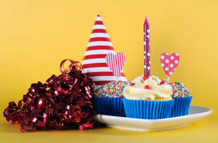Bright and cheery red blue and yellow theme cupcakes with hundred and thousands candy topping and heart toppes for birthday or special occasion on yellow background