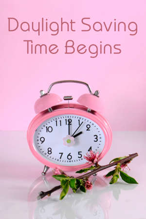 Daylight savings time begins clock concept for start at Spring against a pink background, with text message.