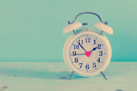 Retro vintage style classic white alarm clock on vintage blue background for daylight saving or time concept.