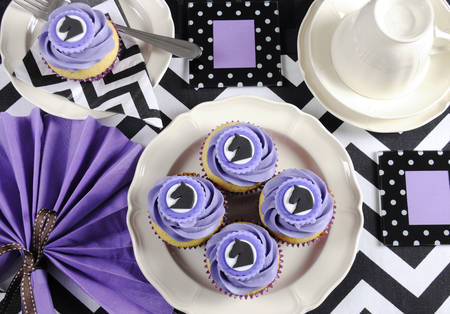 Black and white chevron with purple theme party luncheon table place setting for Melbourne Cup, Australian public holiday, horse race event - with cupcakes.