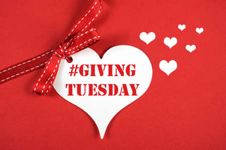 Giving Tuesday philanthropy day after Black Friday shopping message sign white heart on red background and sample text.