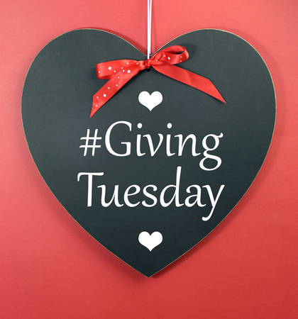 Giving Tuesday message greeting on black heart shape blackboard against a red background.