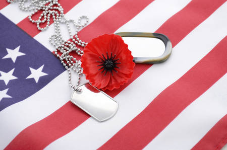 USA Memorial Day concept with dog tags and red remembrance poppy on American stars and stripes flag.