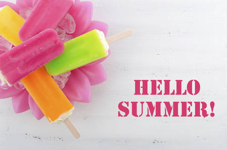Summer is Here concept with bright color ice pop, ice creams with Hello Summer text.
