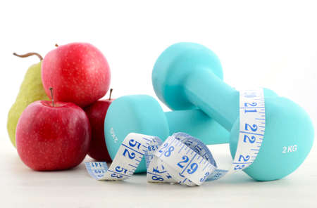 Health and fitness concept with blue dumbbells, tape measure and  fresh fruit on white distressed wood table background.