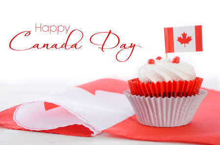 Happy Canada Day celebration cupcake with red and white Canadian maple leaf flag on white wood table, and sample text.