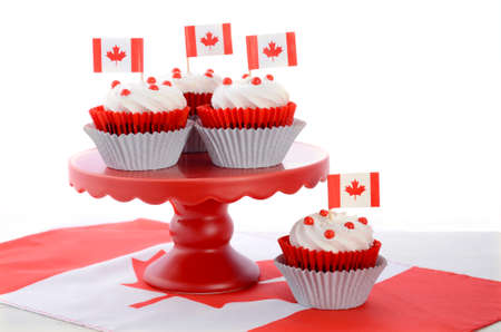 Happy Canada Day celebration cupcakes with red and white maple leaf flag on red cake stand against a white background.