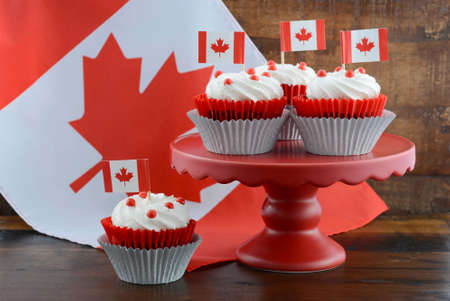 Happy Canada Day celebration cupcakes on red cake stand with red and white maple leaf flag against a rustic distressed wood background.